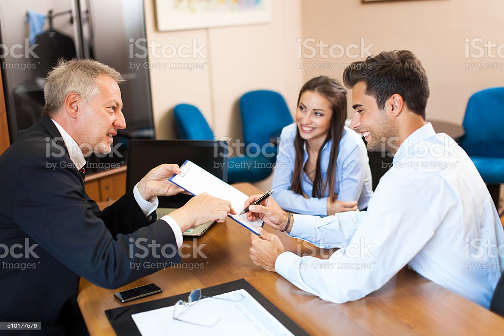 Businessman showing document to a couple stock photo