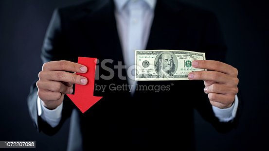istock Businessman showing dollar banknote and red arrow sign falling, financial crisis 1072207098