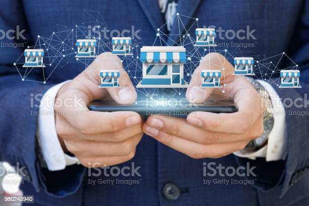 Businessman Showing Franchise System On A Mobile Stock Photo - Download Image Now