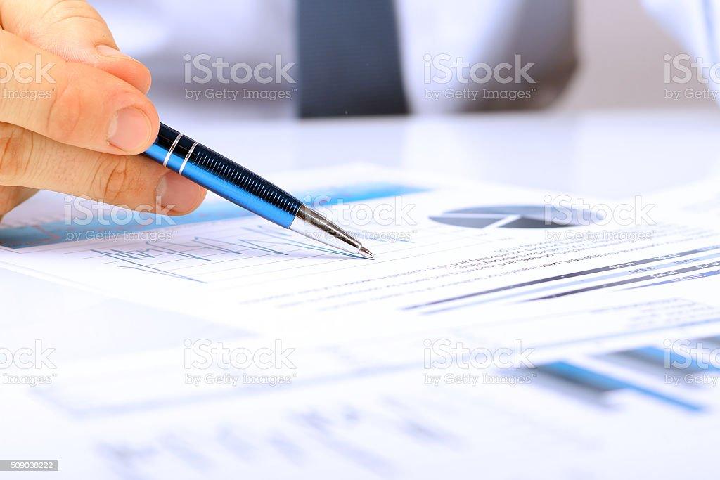 Uomo d'affari mostrando grafici con una penna - foto stock