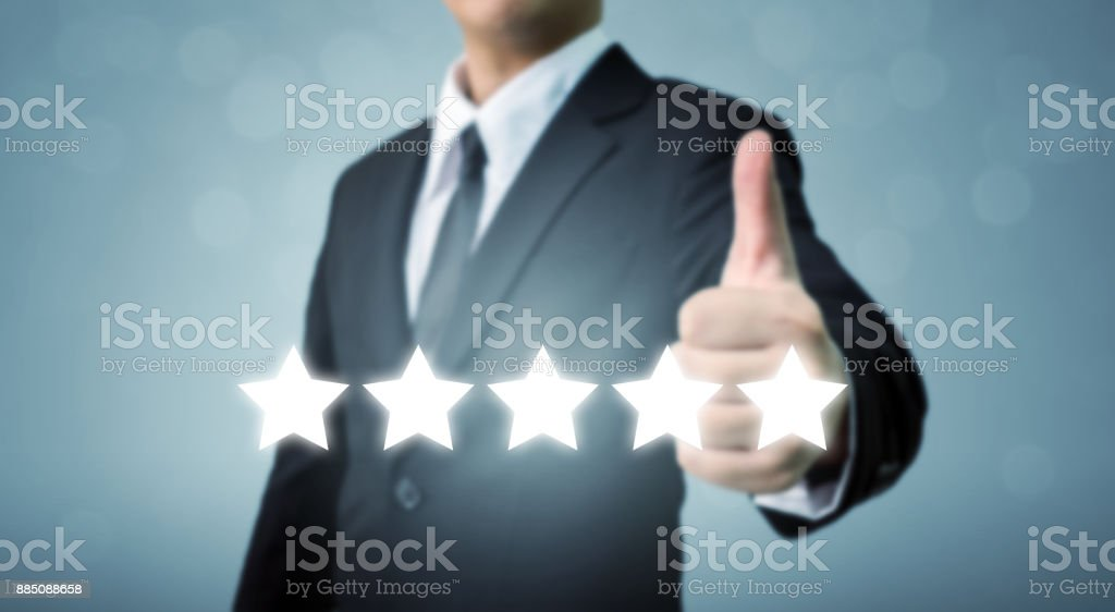 Businessman showing hand sign thumb up and five star symbol to increase rating of company, The excellence of the business or service concept stock photo