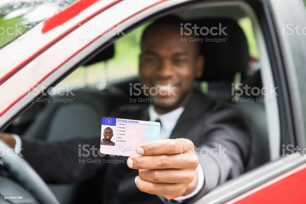 Businessman Showing His Driving License From Open Car Window stock photo