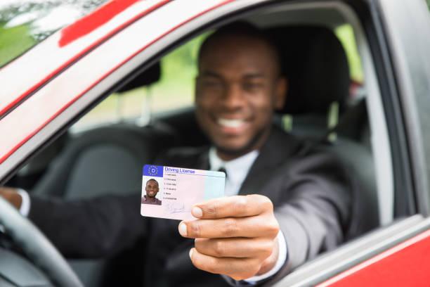 geschäftsmann, zeigt seinen führerschein aus offenen autofenster - führerschein stock-fotos und bilder
