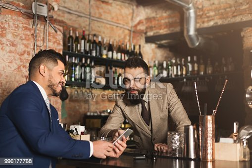 istock Businessman showing information on phone to barman 996177768