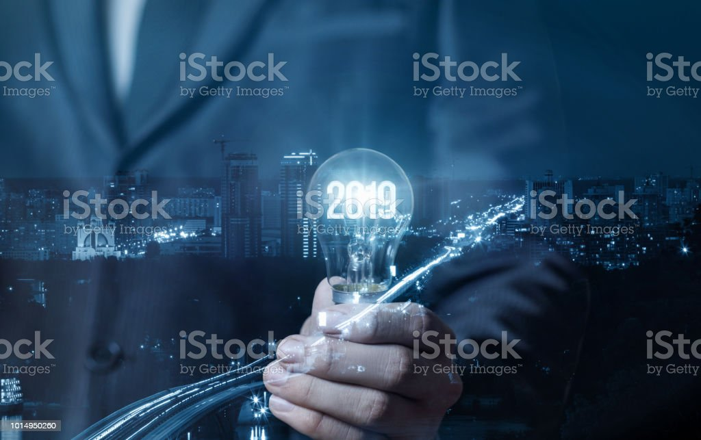 Businessman showing light bulb with glowing 2019. stock photo