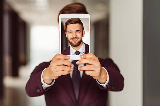 businessman showing selfie on tablet - verduisterd gezicht stockfoto's en -beelden