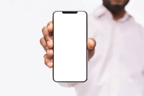 Businessman showing smart phone, with copy space Black businessman showing smartphone with blank screen, isolated on white background, copy space showing stock pictures, royalty-free photos & images