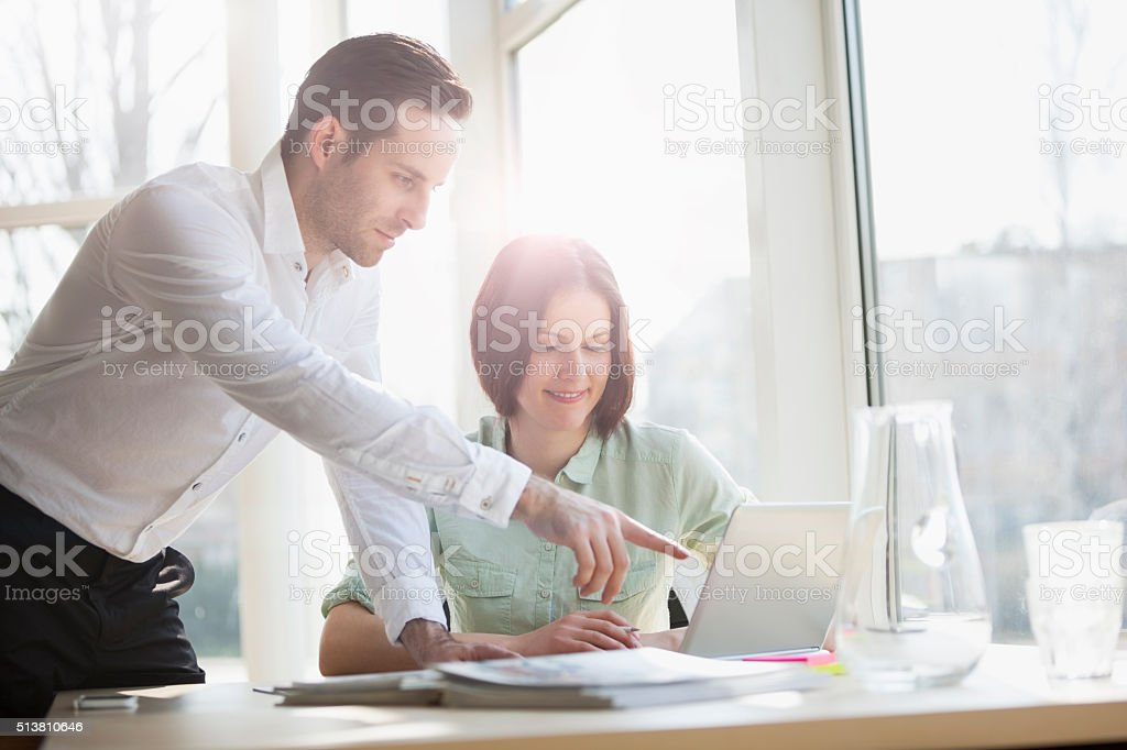 Businessman showing something to female colleague on laptop stock photo