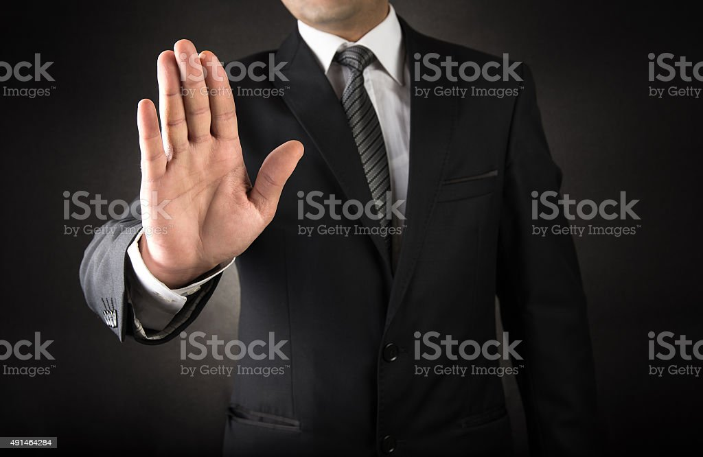Businessman showing stop sign stock photo