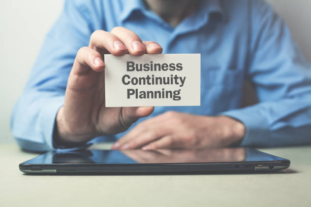 homme d'affaires liste texte business continuity planning sur carte de visite. - continuité photos et images de collection