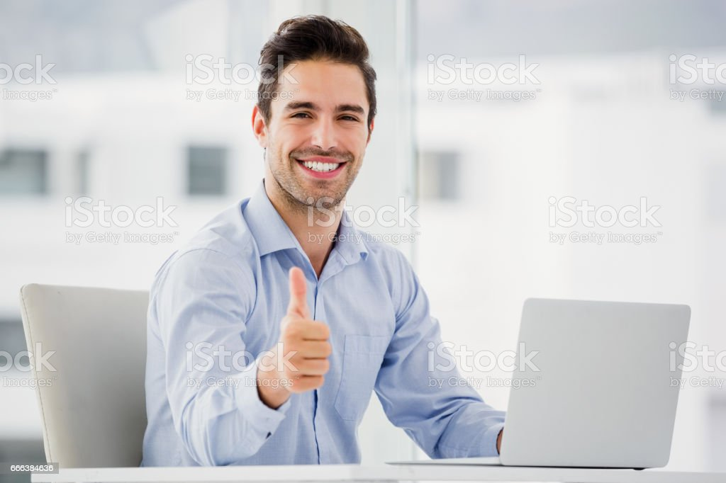 Businessman showing thumbs up while using laptop stock photo