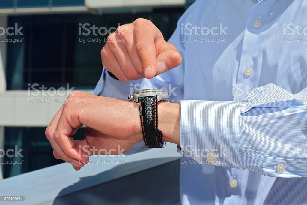Businessman showing time on his watch. Its time concept stock photo