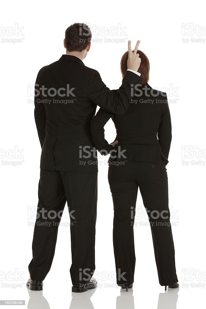 Businessman showing victory sign behind a businesswoman stock photo