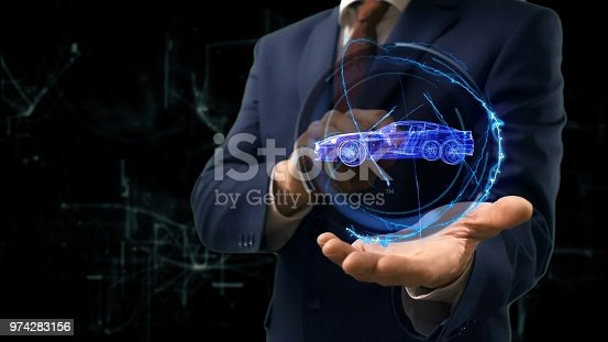 istock Businessman shows concept hologram Car on his hand 974283156