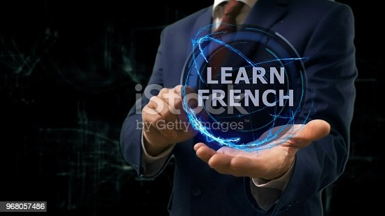 Businessman shows concept hologram Learn French on his hand. Man in business suit with future technology screen and modern cosmic background
