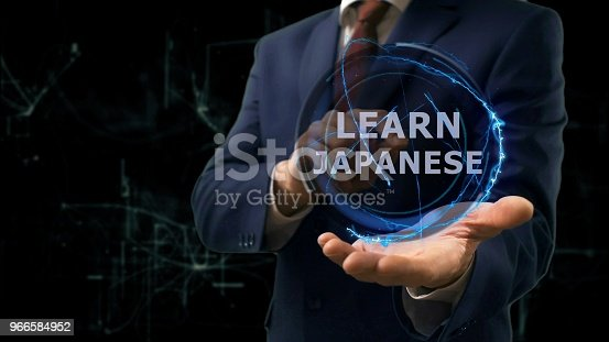 Businessman shows concept hologram Learn Japanese on his hand. Man in business suit with future technology screen and modern cosmic background