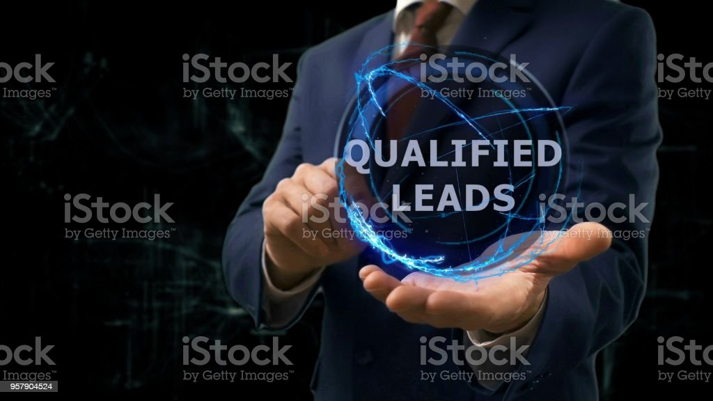 Businessman shows concept hologram Qualified leads on his hand stock photo