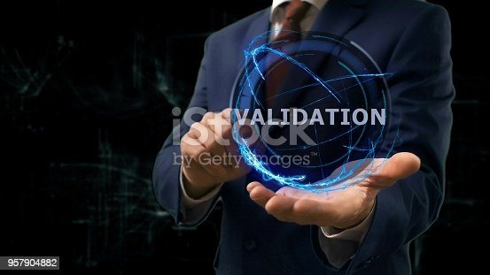 Businessman shows concept hologram Validation on his hand. Man in business suit with future technology screen and modern cosmic background
