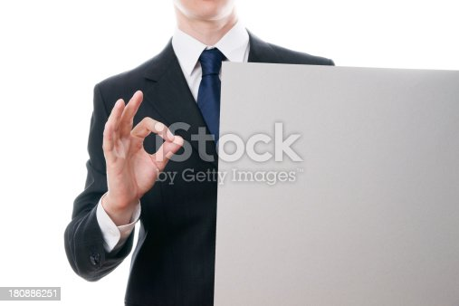 istock Businessman shows OK sign and holds blank sheet of cardboard 180886251