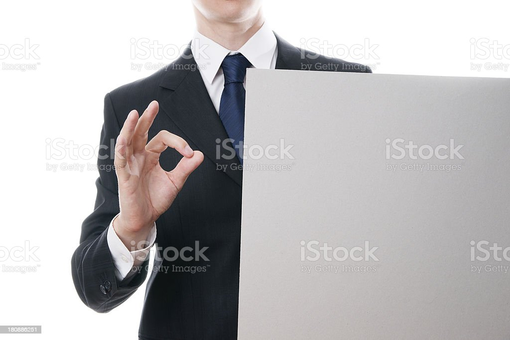 Businessman shows OK sign and holds blank sheet of cardboard stock photo