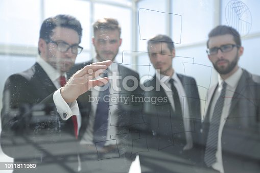 istock businessman shows the business team a new marketing plan 1011811960