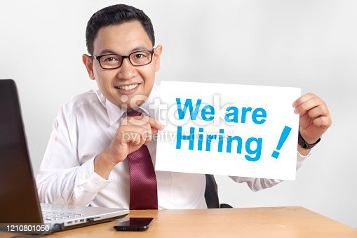 1153648747 istock photo Businessman Shows We Are Hiring Announcement 1210801050