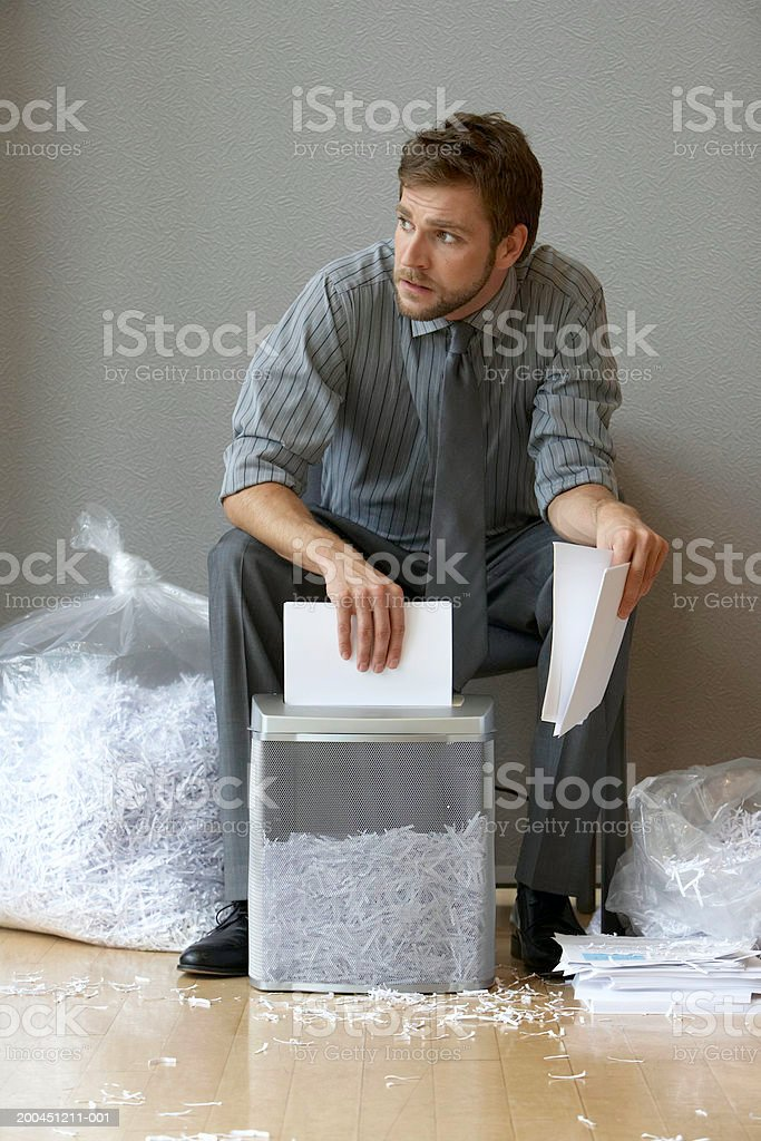 Businessman shredding documents, looking away stock photo