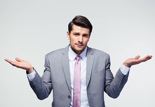 Businessman shrugging shoulders Businessman shrugging shoulders over gray background. Looking at camera shrugging stock pictures, royalty-free photos & images