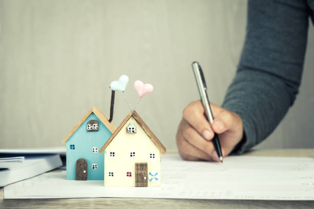 Businessman signature in documents graph chart checking document in property investment project on desk office. Report selling in mortgage agent marketing in real estate concept. Home Driftwood Ideas stock photo