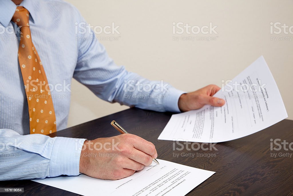 Businessman signing a contract stock photo