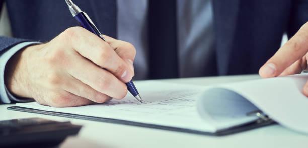 Geschäftsmann, der ein Dokument signiert, Notizen macht, einen Fragebogen ausfüllt oder Korrespondenz schreibt. Nahaufnahme der Hand des Mannes und der Zwischenablage. – Foto