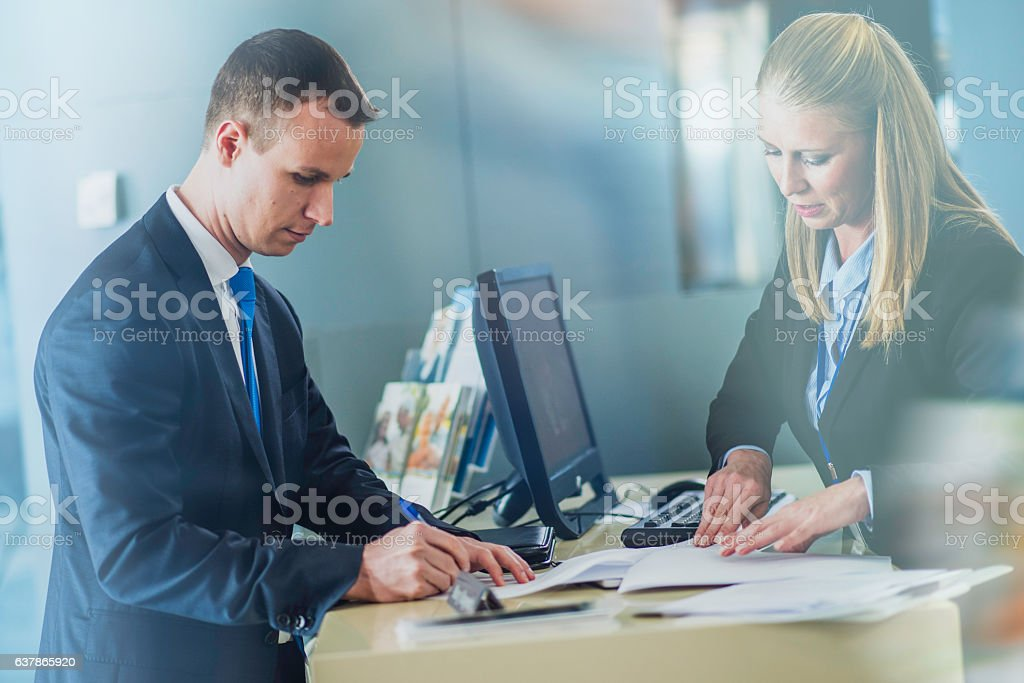 Businessman signing an insurance contract at a counter - Photo