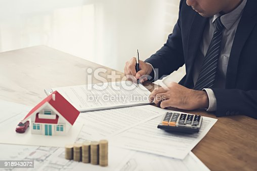 istock Businessman signing contract agreement with money and house model on the table 918943072