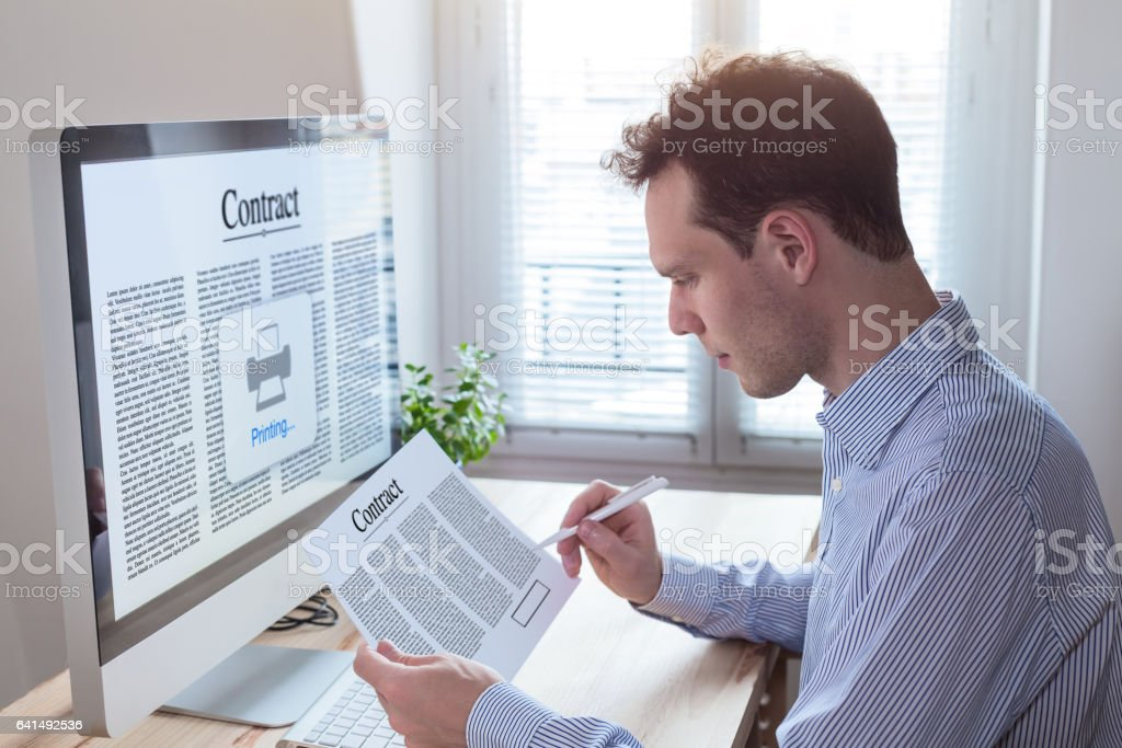 Businessman signing contract and reading terms and conditions in office stock photo