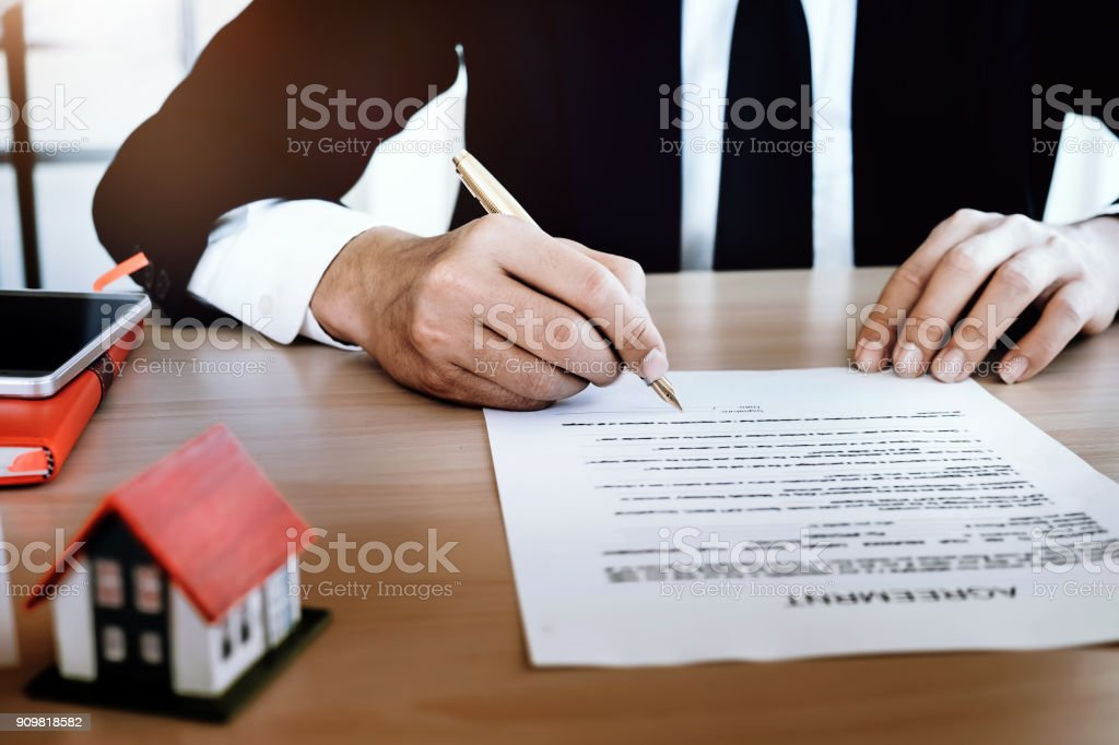 businessman signing document concept, focus on male hand holding pen, putting signature on legal document, Agreement, contract and insurance concept for Trading estate. stock photo