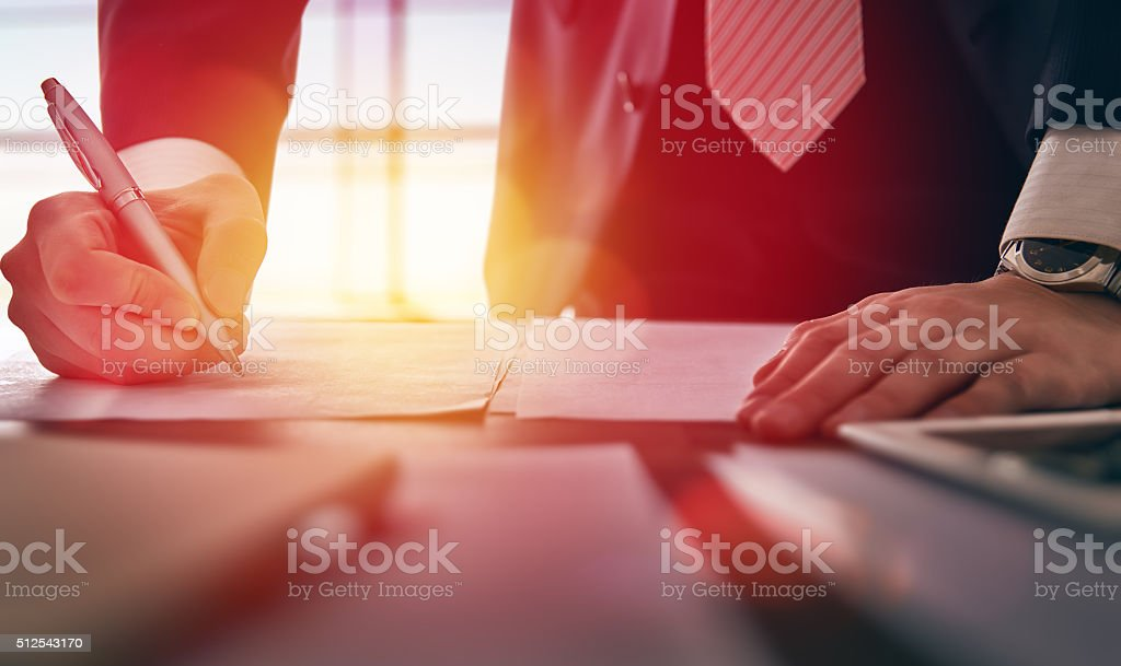 businessman signing documents stock photo
