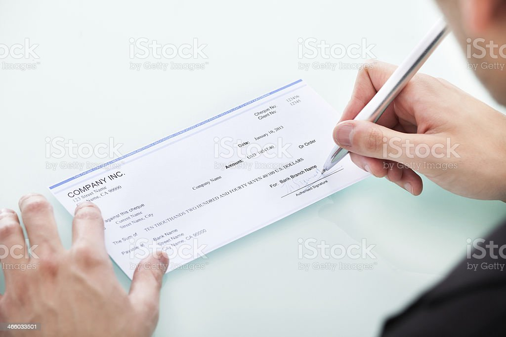 Businessman Signing On Cheque stock photo