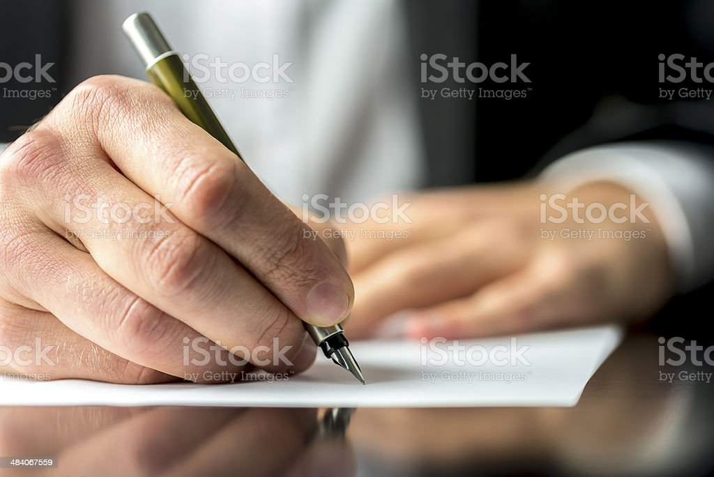 Businessman signing or writing a document stock photo