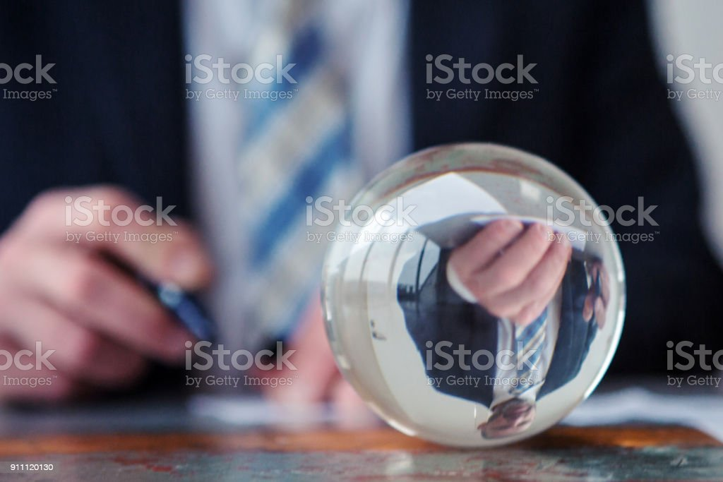 businessman signing papers in front of glass ball stock photo