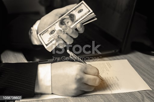 istock Businessman signs documents and holds dollars in his hand. Business deal, project. Signing a contract. Concept of finance and investment. Affiliate program. Credit. Property taxes 1058738602