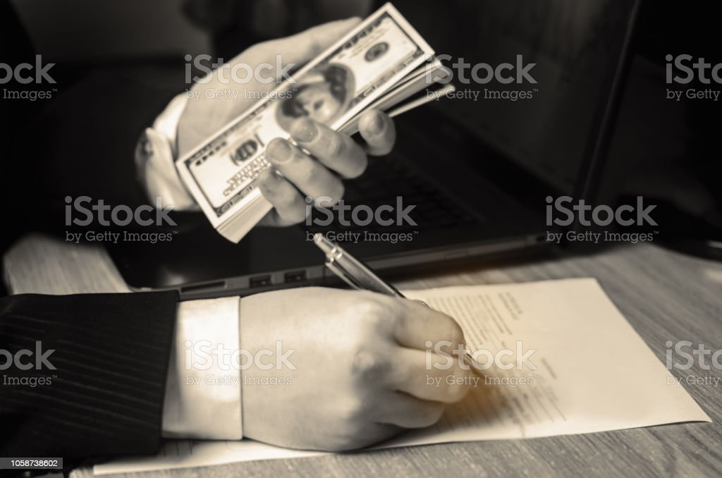 Businessman signs documents and holds dollars in his hand. Business deal, project. Signing a contract. Concept of finance and investment. Affiliate program. Credit. Property taxes stock photo