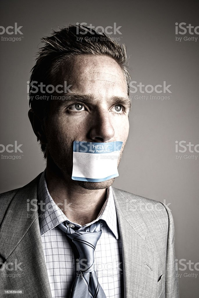 Businessman Silenced by Name Tag stock photo