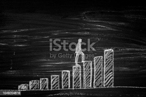 istock Businessman silhouette climbing chart bars 1049204816