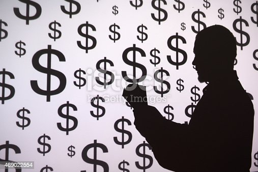 Man standing in front of a projection screen displaying dollar signs.