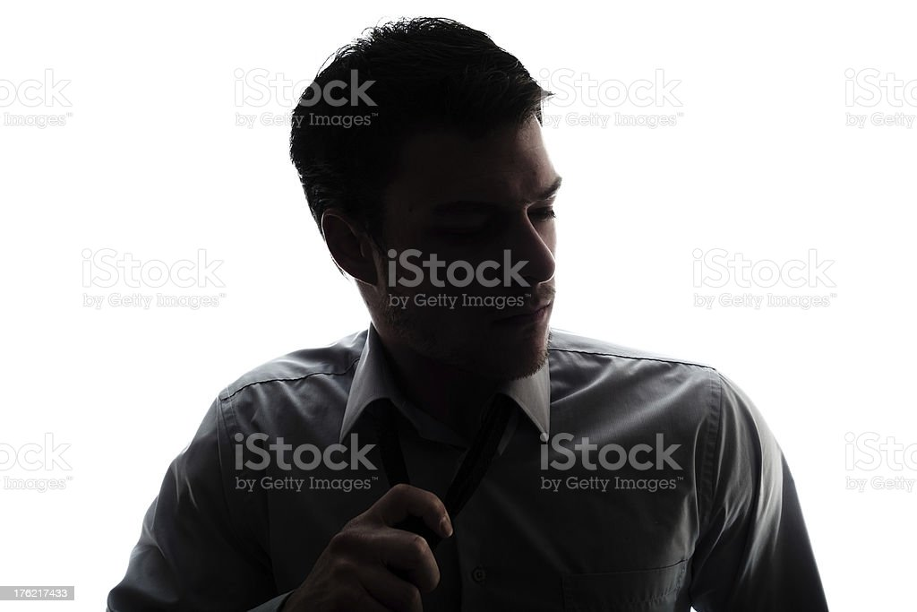Businessman silhouette loosen a bit the tie after work stock photo