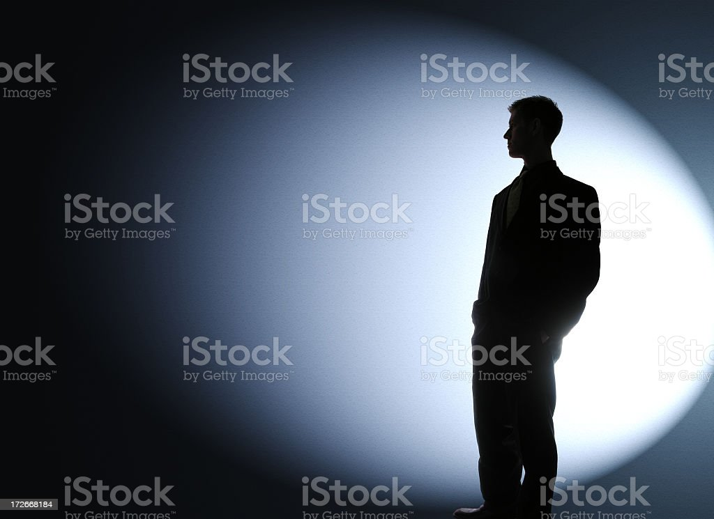 Businessman silhouetted in a spotlight stock photo
