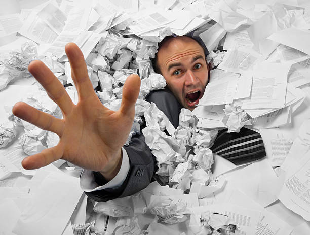 Businessman sinking in heap of documents stock photo