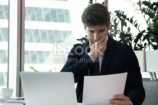 639105488 istock photo Businessman sit at desk holding paper reading letter feels frustrated 1226412413