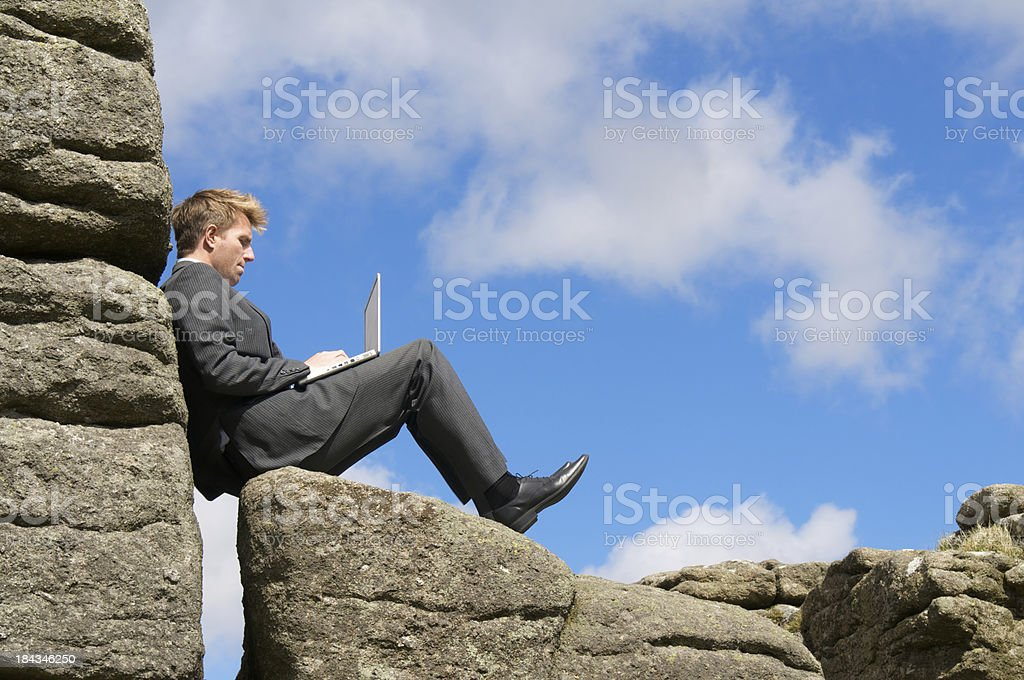 Businessman Sits at Rocky Perch Typing on Laptop royalty-free stock photo