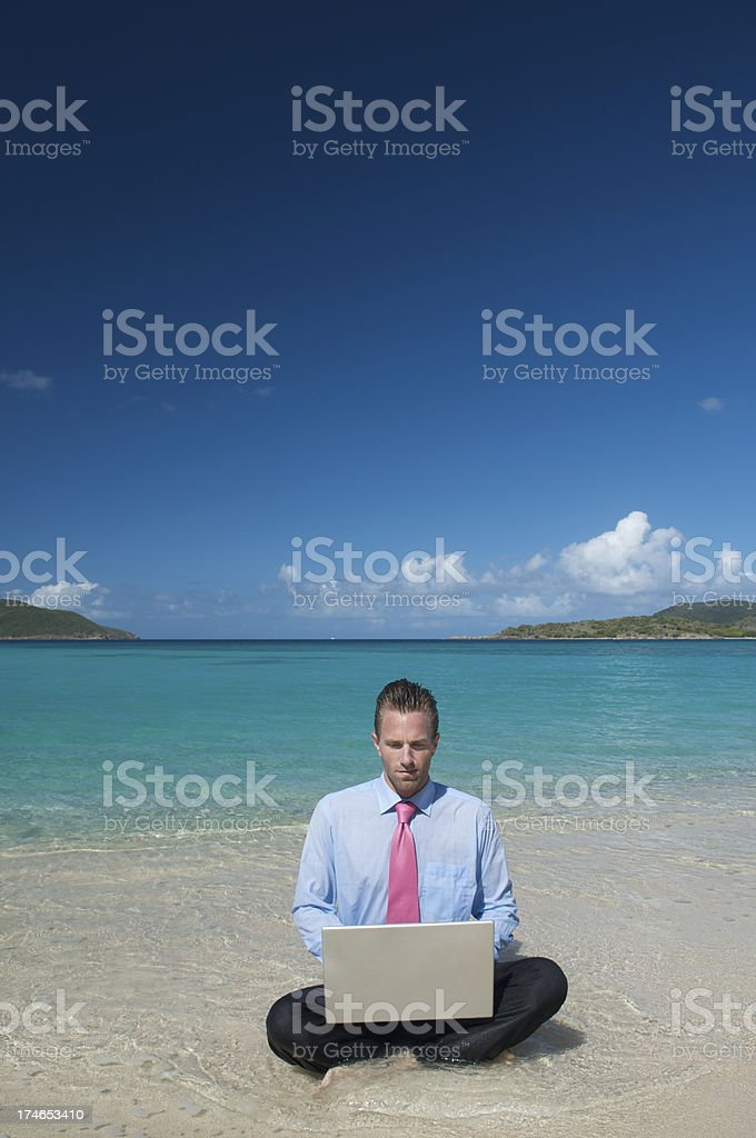 Businessman Sits at Tropical Beach Working on Laptop in Waves royalty-free stock photo
